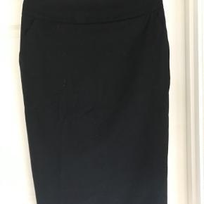 Varetype: Pencil Farve: Sort Oprindelig købspris: 1000 kr.  Super flot og klassisk pencil nederdel. Lommer i siden og slids bagpå. Går til under knæet.