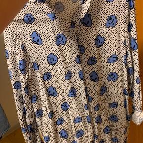Skjorte med små sorte prikker og blå blomster. Den er stor i størrelsen .  Køber betaler fragt.