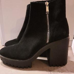 Sorte ruskinds støvler. Brugt få gange, da de er få små. Har et lille mærke på venstre sko, bagerst.