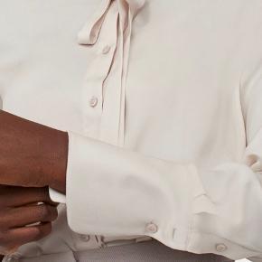 Langærmet skjorte med kinakrave, smalle bindebånd og og knapper foran.  Dobbelt bærestykke med læg og skæring i ryggen. Bred manchet med knaplukning nederst på ærmerne. Rundet kant forneden.  Lys muldvarp farve.  100 % polyester, vask 40 grader.  Fejlkøb, er ikke pakket ud af posen endnu.