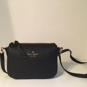 Jeg sælger en sort crossbody taske fra Kate Spade. Tasken er købt på zalando, i sommeren 2018, nyprisen er 1795kr.  Tasken sælges da jeg ikke får brugt den nok, maks 3 gange og den er i perfekt stand.   Inkluderet med tasken er den originale dustbag, en careguide og fyld til at have i taske når den ikke bruges, til at holde formen.   Målene på tasken (fundet på nettet: Højden= 14cm  Længde= 19cm Dybde= 7cm  Remmen= 54cm   (Fra røgfrithjem)