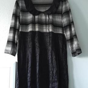 Flot sort tunika møstret top. Brystvidde ca 2x 55 cm og længde ca 86 cm. Matr 65% polyester og 35% bomuld