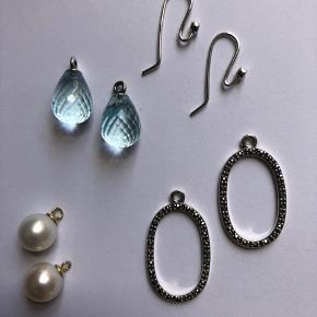 Pandora ørebøjler i sterlingsølv med tilhørende 3 forskellige vedhæng til at lave smukke kombinationer. *Runde perler m.14 kt. Øskner *Åbne vedhæng m. facetter. Sælges kun som samlet sæt. *Dråbeformede faceterede lyseblå sten.