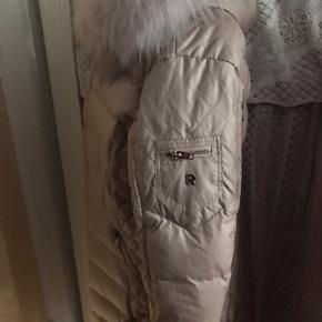 Ny med tags.  Smuk Rock and Blue jakke i luksus kvalitet med dun og slim fit  90 cm lang. Guld lynlåse. Model Ciara.  Farve: Champagne, creme. Str. 46 (L, XL, XXL). Nypris 3.399 kr.