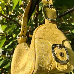 Sælger min flotte DKNY taske i den sjældne gul, den er vintage og købt her på Trendsales - jeg sælger fordi jeg ikke får den brugt nok.   Rigtig fin stand, der er lidt slid ved lynlås og pletter i foret indeni.