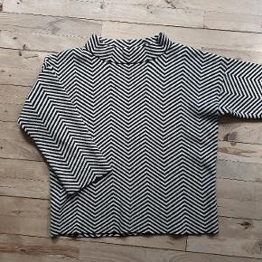 Lindex bluse med grafisk mønster af super kvalitet.  Den er sort/hvid og det er fin strik men alligevel tykt ( dobbeltlag). Den måler 110 om brystet, og er 59 lang.