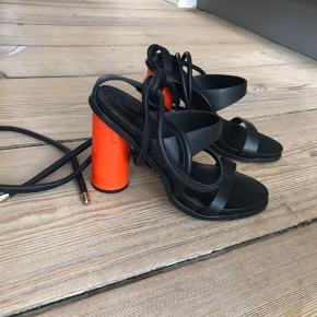 Stiletter fra By Malene Birger. Brugt en enkelt aften og fejler intet. Ganske få små sorte mærker på det orange.  Det orange kan nok pilles af hvis man ønsker en sort hæl i stedet.  Bytter ikke.