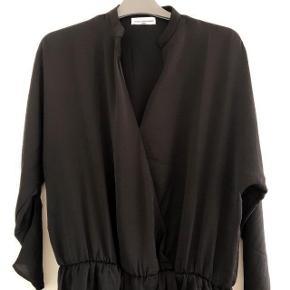 Moss Copenhagen sort foret kjole str M med elastik i taljen. Har er ca-brystmål 2x 47 cm og længden er 94 cm. Let kvalitet 100% polyester
