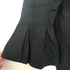 Flot bluse med havfrueærmer i 3/4 længde. Mørk, støvet grøn.