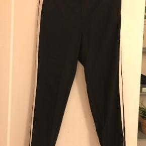 Sorte bukser med hvid stribe ned ad benet. Str. M/32.