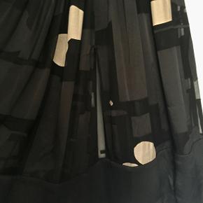 Se alle 4 billeder i fuld størrelse Eksklusiv nederdel , Stine Goya, Sort m/guld, Silke/viskose , Næsten som ny  Eksklusiv nederdel fra STINE GOYA (model Kirsten) i elegant løst vidde design i smukke farver og let transparent burn out mønster samt i en behagelig viskose/silke kvalitet. Nederdelen har fast talje samt smuk lang længde med bred effekt kant for neden. Blot brugt enkelte gange og er uden brugstegn. Længde: ca. 75 cm. Linning er ca 4 cm og måler 38-39 cm fra side til side (svt livvidde på 76-78 cm). 30% silke, 70% viskose - håndvask eller rens. Nypris ca 2100 kr.