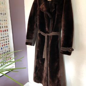 Super lækker frakke med en fin blanding af ruskind og fake fur. Den er brun med ruskindsbælte til. Frakken lukkes med hægter.