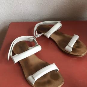 See by Chloé sandaler i hvidt læder med lædersåler.  Str. 38.  Lukkes med velcro rundt om anklen.   Spæner gået lidt fra foran.  Dustbag medfølger.  Brugt få gange - ingen lugt.
