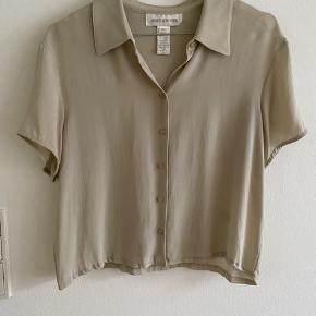 Vintage/ retro/ secondhand/ genbrug bluse/ top/ kortærmet skjorte i beige.    100% silke   I god, smuk vintage stand.   Kan passes af en xs-m  Længde: 50 cm Bryst: 48 cm x 2 Talje: ca. 46 cm x 2  Kan sendes eller afhentes i Mårslet eller Aarhus C efter aftale.