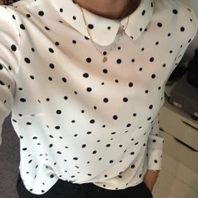 Fin skjorte med sorte prikker. Lynes i nakken og har en fin skjorte kant foroven. Str. S.