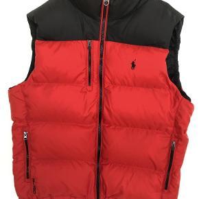 Varetype: Dunvest Farve: Sort og rød  Dunvest fra Polo Ralph Lauren. Vesten er enkel i modellen med 3 frontlommer, to-farvet rød og sort med lynlåslukning. Vestens logodetaljer er broderet på brystet. En rigtig lækker vest af den bedste kvalitet.