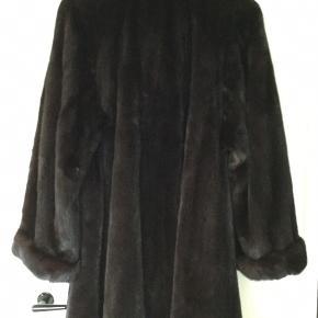 Saga Mink, superb quality farmed mink - A Touch Of Skandinavien. A- vidde falder virkelig flot. Smuk mørkebrun mink jakken har store stiklommer, sjalskrave, ærmer med opsmøg samt hægtelukning. Indvendigt med Mørkebrun/sort foer.. Str. ca. 40/42/44 Længde ca. 98cm, ærmelængde ca. 68 cm, brystbredde målt fra under ærme til under ærme 62 cm. x 2 - Vidde forneden ca. 100 cm. x 2. Fremstår som ny. Ingen brugsspor. Fra ikke rygerhjem.  Bemærk skambud besvares ikke.  Købt i KBH. Kvittering haves ikke længer.  Sender gerne flere billeder.