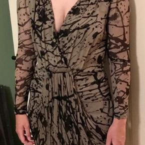 Flot kjole med grafisk mønster. 100 procent silke og et tyndt underskørt i viskose.  Kjolen falder flot med draperinger og små skulderpuder. (Se billeder)  Jeg bytter ikke og returnerer ikke. Men du er velkommen til at komme forbi og prøve den ☺️
