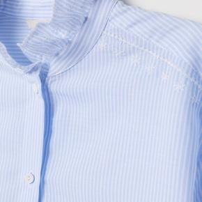 Skjorte med fine broderede flæsedetaljer fra H&M trend.  Brugt få gange. Bytter ikke.