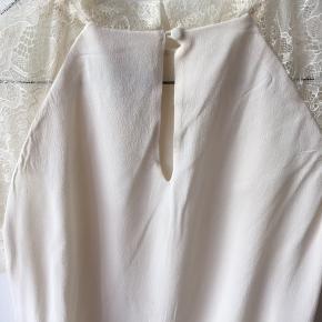 Romantisk top med fine blondeærmer og en lille opretstående halskrave. Løst siddende. Lukkes med lille knap i nakken