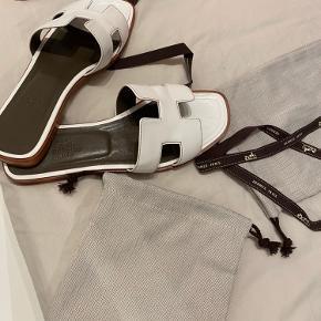 Smukke klassisk Hermes Oran sandaler i hvid. Fremstår som nye, på trods af bunden som har ganske lidt slid. Byd