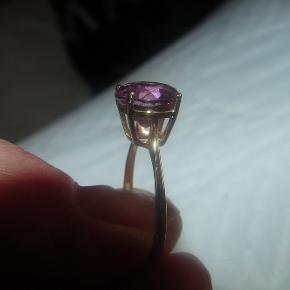Rocks & co  Flot guldring med en 3.2ct stor rund Spanish Pink Fluorite. Synes nu den mere er lyselilla ind den er pink. Ringen er i 9 karat guld og er en størrelse DK.54 / 17mm. Der medfølger certifikat. Se også halskæden jeg har til salg, som passer til ringen.