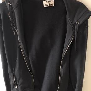 Rigtigt fed Acne Studios hoodie i sort! Hoodien er XS, men den fitter M, jeg er 175 og den passer perfekt. Eneste flaw er at lynlåsen driller, så den går fra hinanden. En med forstand på det, er jeg dog sikker på vil kunne fikse det. Byd, så finder vi ud af noget :-)