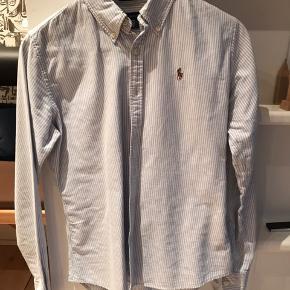 Klassisk skjorte i slim fit i str. 6 som cirka svarer til 36. Farven er blå/hvid stribet