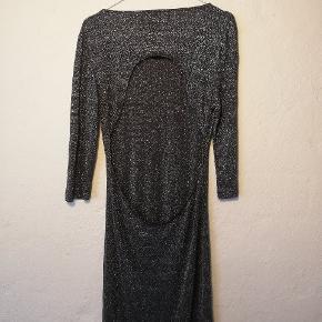Kjolen har en dyb ryg og den går til midt på låret