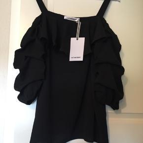 Ubrugt smuk bluse med justerbare skulderstropper. Fin både til sommer og julefesten:) stadig med tags