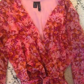 Blomstret kjole fra Vero Moda - brugt og vasket én gang i sommers. Farver: pink, lyserød, orange og lilla. Elastik under bryster, bånd/bælte og flæsekant for neden - lidt kortere foran end bagved