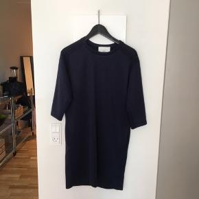 Flot enkel kjole fra Mads Nørregaard, med fine detaljer i lommen og ved skulderen.