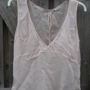 Varetype: bluse Farve: fersken  En tynd top med pyntesten. Den har v udskæring. Den er gennemsigtig. 100% viscose.