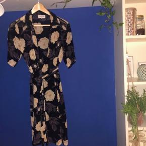 Flot Ganni skjortekjole med bindebånd i taljen. Et par år gammel og brugt, kan du kun ses ved kjolens nederste knap hvor stoffet er rykket lidt (det ser man ikke når kjolen er på) kun vasket i hånden.   BYD