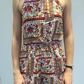 Mønstret playsuit fra H&M's Coachella-kollektion med bindedetalje på ryggen. Str. 38, men fitter også en 36
