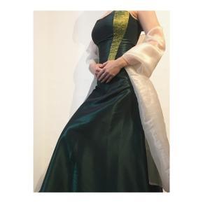 Todelt gallakjole med nederdel og corsage.  Corsagen er med snører i ryggen, og størrelsen kan derfor varieres.  Sættet er skræddersyet.  Samlet pris 600 kr uden stola  Pris for stola 100 kr