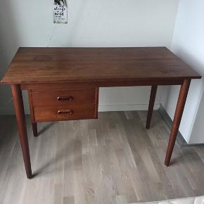 Mindre skrivebord i teak med 2 skuffer. Har mindre skader og trænger til en slibning. Mål. Længde 105cm, dybde 51cm og højde 74cm.