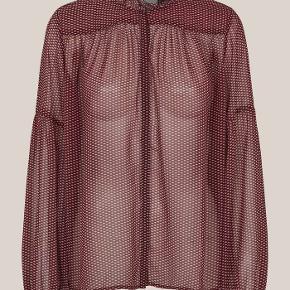 Denne skjorte er fremstillet i en sart polyesterkv alitet med smukt all-over print. Skjorten har flæs er ved udskæringen med takkede kanter og en skjult knapstolpe. Den har vide ærmer og lige søm forned en.