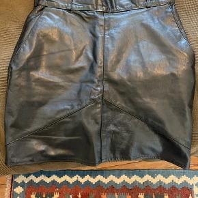Skind nederdel i str. 36 Den har været gået op i en syning, men jeg har selv syet det. Ellers er der ingen slid.