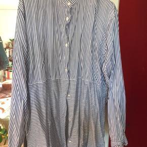 Fin blå og hvid stribet skjorte. Lidt stor i størrelsen, men dog alligevel for lille til mig, derfor sælges den.