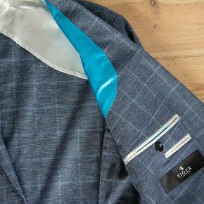 Flot blazer i 100 % uld. Let sommermodel. Støvet blå (nærmest jeansfarvet) med lysere blå tern. Style Evert 10BZ. Meget fin stand.