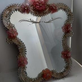 Så smukt gammelt Murano spejl sælges. Spejlet kan både hænge på væggen eller stå på bordet afhængig af, hvordan det ønskes at benyttes. Spejlets højde er 42 cm og spejlets bredde er x 36 cm. Pris: 2400kr afhentet eller plus porto.