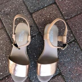 Høje sandaler fra Tommy Hilfiger, med logo et sted. De kan justeres i str. oppe ved ankelen. Køber betaler fragt.