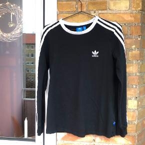 Sort langærmet trøje fra Adidas med de ikoniske striber. Den er meget velholdt. Størrelse medium. Kan hentes i København eller sendes