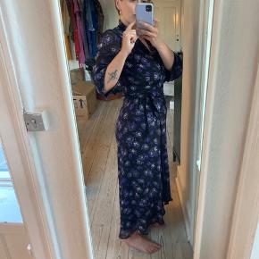 Smuk kjole fra Ganni kun brugt en enkel gang. Den går til ankel/gulv bagpå og lidt højere op foran. Sort med smukke lilla blomster-mønster. 100% viskose. Fejler intet. Bud er velkomne