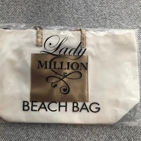 """Lady Million beach bag i hvid canvas med lomme og hanke i """"guldlæder""""  Prisidé dkk 100,00 - kom gerne med et seriøst bud.  Forsendelse med DAO dkk 35,95"""