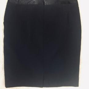Klassisk, elegant pencilskirt med for, lommer, og fint detalje som skindende material i livet.   Str.40  Længde ca 56cm Livvide ca 88 cm  80% uld, 20% polyester  Kun prøvet på nogle gange.
