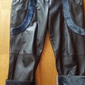 Sorte Skindbukser fra Great Greenland i str. 42  Sorte skind 3/4 lange bukser med sælskind, to lommer foran de er fra Great Greenland, designet af IsaksenDesign.  Vildt flotte, har kun brugt dem 1 gang, kan desværre ikke passe dem. Er en lille XL, er 98 cm i livet  Ny pris 6000,-