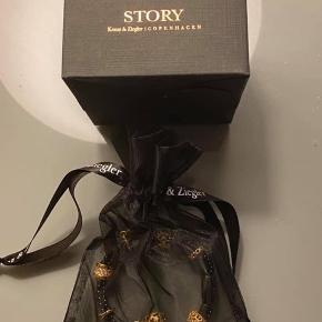 Kranz & Ziegler story Ready to go armbånd  Med 8 guldbelagte charms  Aldrig brugt.  Længde 19cm Nypris ca 3500kr