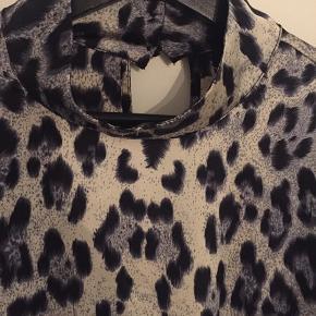 Puls skjortebluse med knap og blonde på ryggen  Farven er blå/sort og creme
